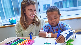 Child life specialist sitting with a child who is drawing