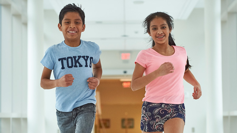 Young boy and girl running down hall