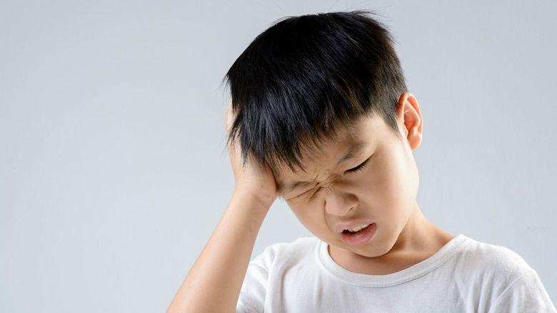 boy rubbing head in pain