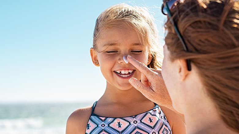 Girl smiling getting sunscreen put on her nose.