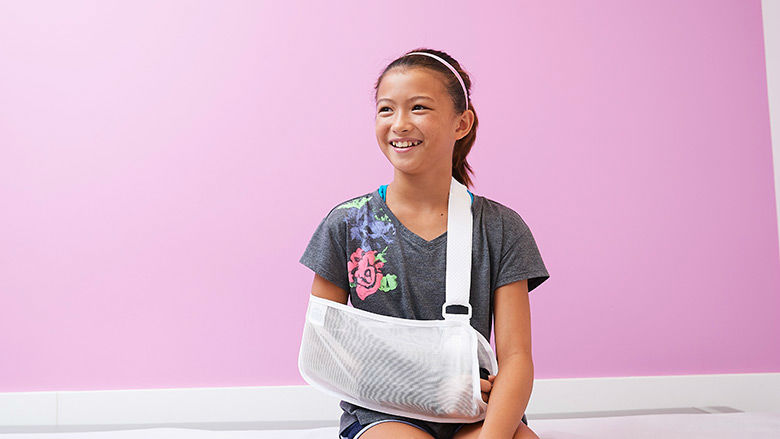 Young girl wearing a sling