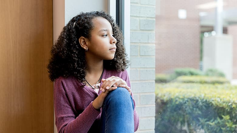 Adolescent girl sadly looking out window