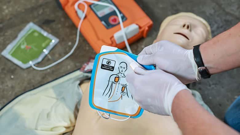 Hands setting up a defibrillator