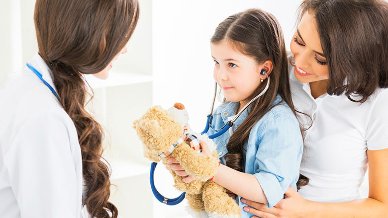 Young girl holding teddy bear and stethoscope