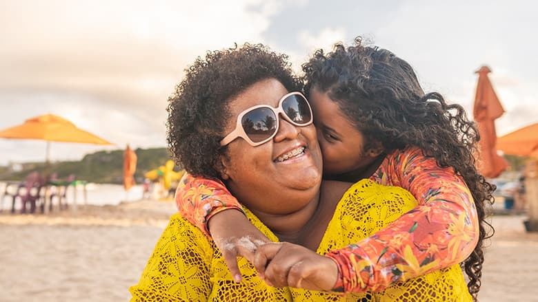 Daughter hugging mother while on the beach