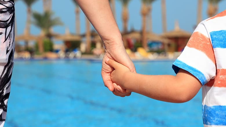 Parent and child holding hands at a pool