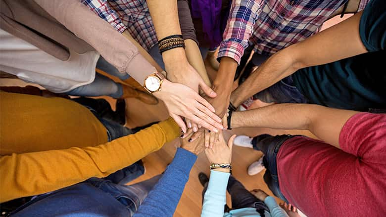 Diverse group of hands coming together