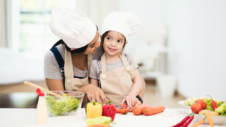 Mom cutting vegetables with daughter