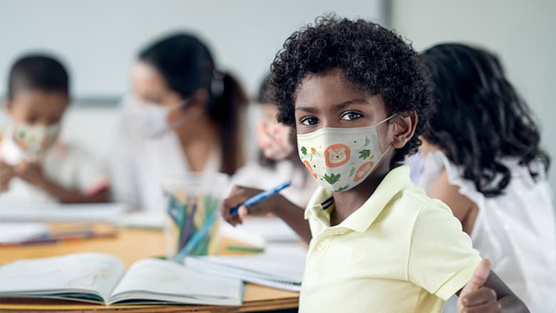 Child wearing protective mask in classroom setting