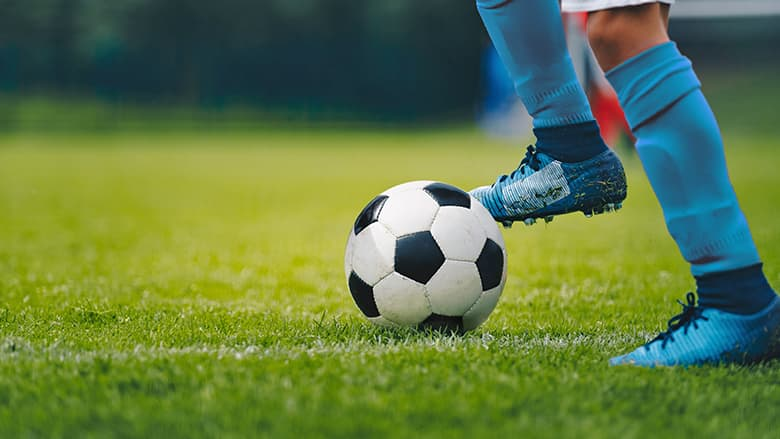 Closeup of soccer player's cleats and soccer ball