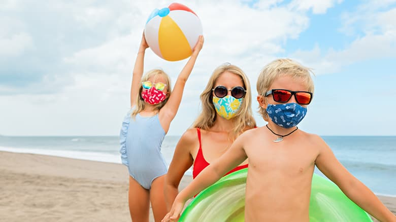 Family on beach wearing masks