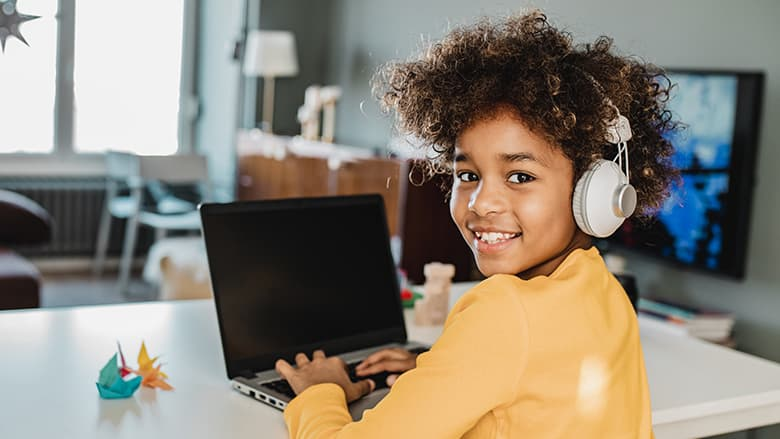 Young girl smiling and using her laptop