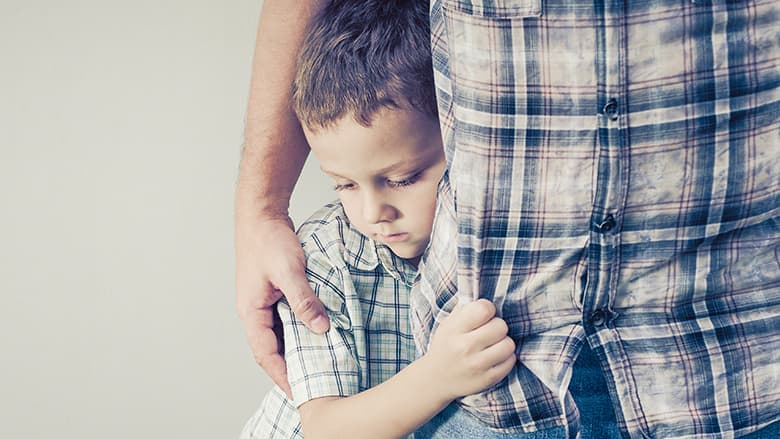 Young boy clinging to parent's leg