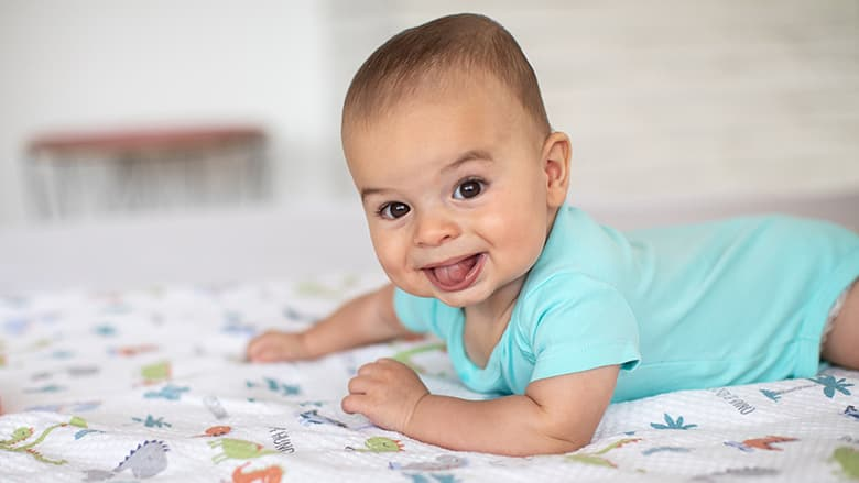 Young baby crawling and sticking its tongue out