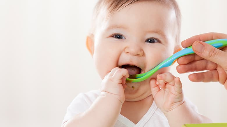 Infant being fed with plastic spoon