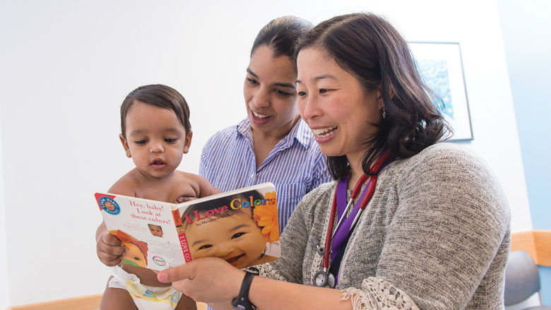 doctor and mother reading to infant