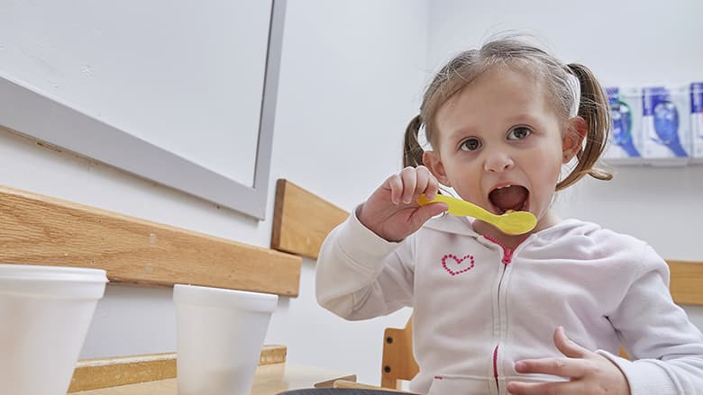 Young girl eating with a spoon