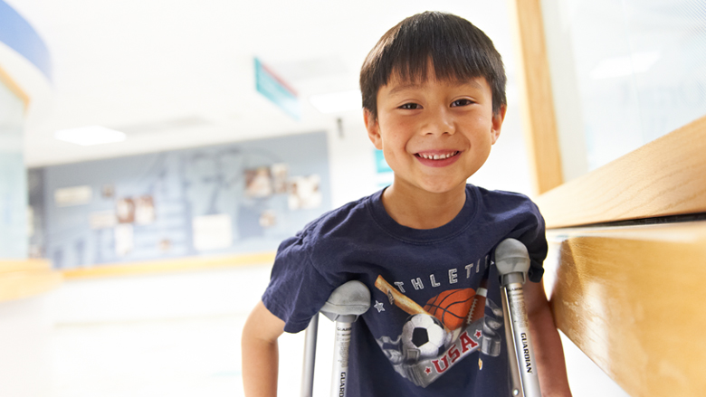young boy with crutches