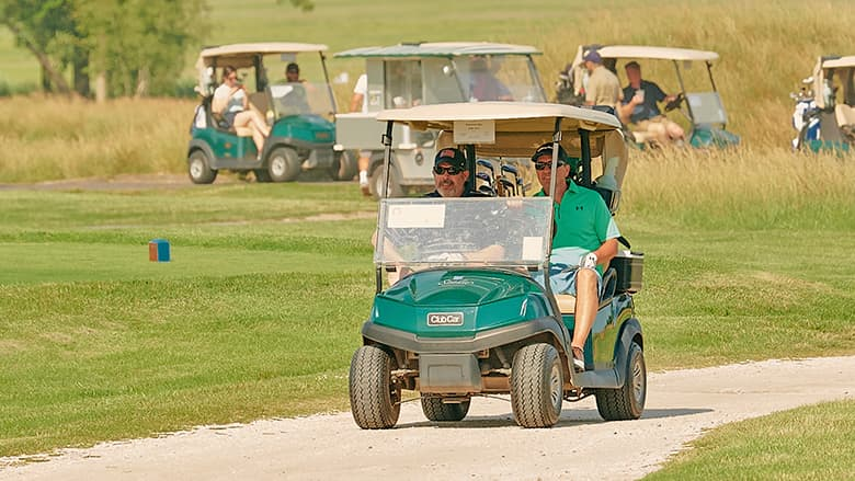 Golfers riding in golf carts