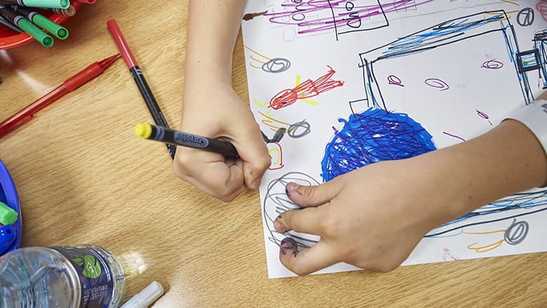 Child's hand coloring a picture