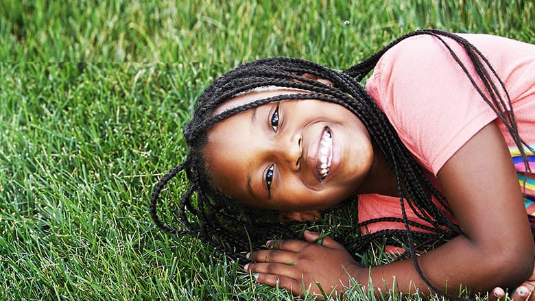 Oncology patient smiling and laying in the grass