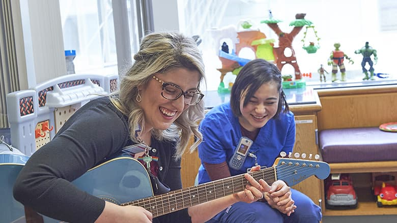CHOP music therapist playing guitar