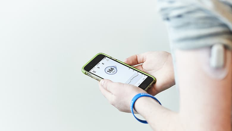 Teen using mobile app to monitor glucose level