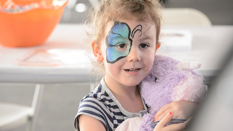 Young girl with a butterfly wing painted on her face