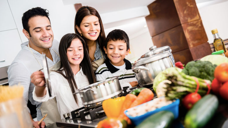 Family in kitchen cooking healthy meal together