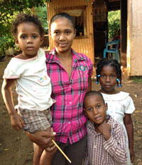 Sandra Carela Jimenez (center) is a health promoter for Niños Primeros en Salud (NPS) in the Dominican Republic, where she helps mothers raise healthier families. Her own children, Ruberky, Ruben and Rubelly (left to right) benefited from care provided by