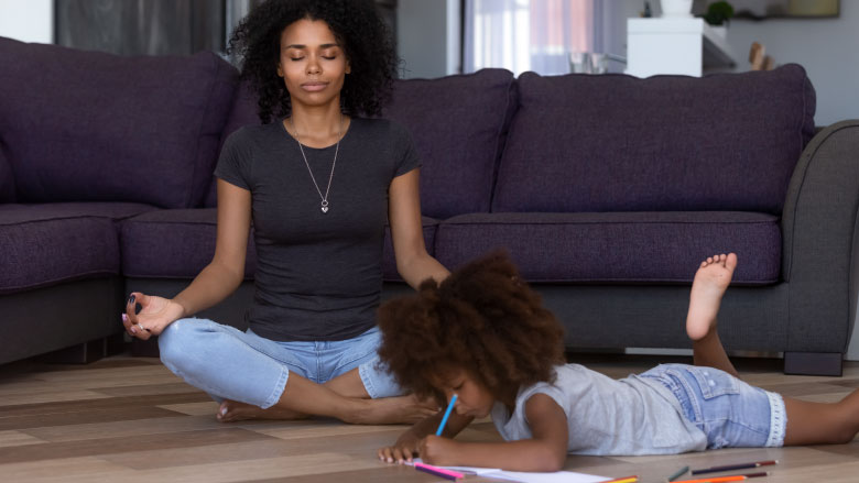 mom meditating while daughter is coloring