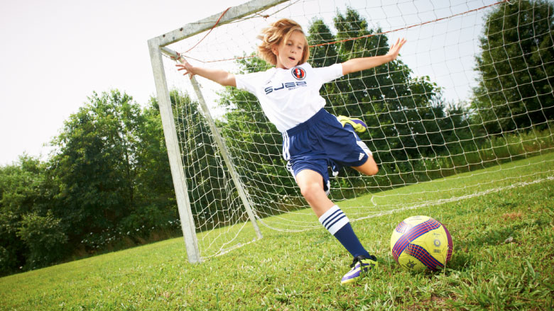 Tween girl playing soccer in front of net