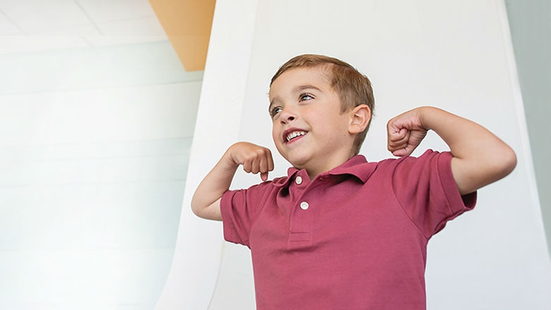 Young boy flexing his muscles