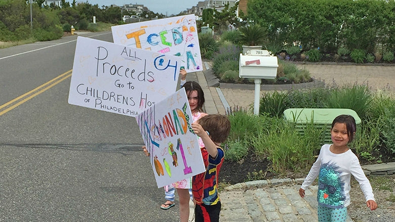 Children holding lemonade signs