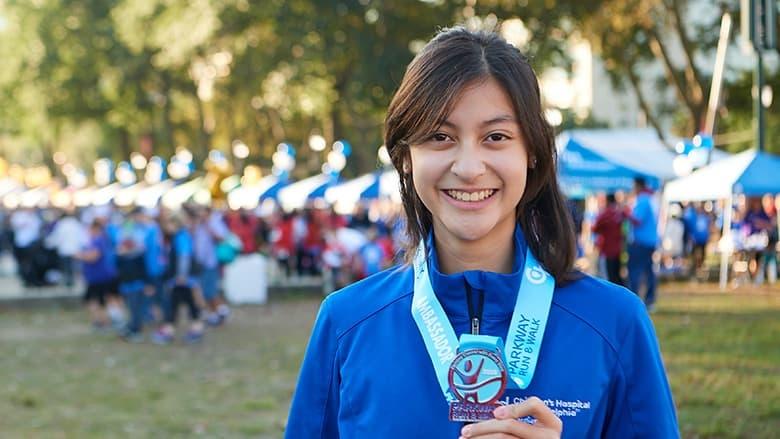 Parkway Run ambassador holding medal