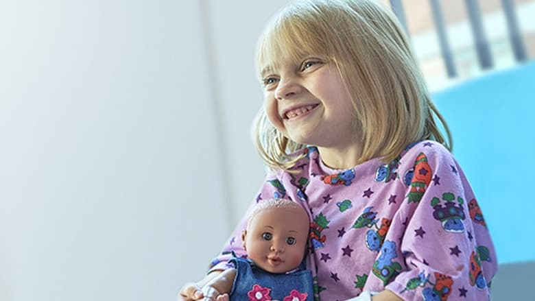 Young hospital patient clutching doll