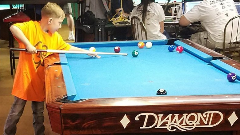 child playing 9 ball at junior 9 ball tournament