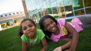 Girls smiling lying in grass