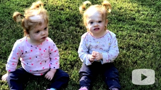 Delaney twins sitting in the grass