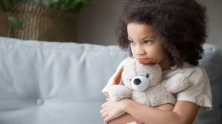Scared young girl holding teddy bear