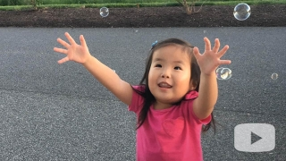 Avery extending her arms reaching for floating bubbles outside