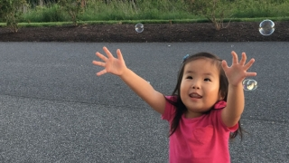 Avery playing with bubbles outside
