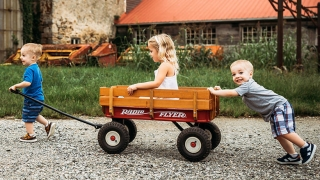 The Barkhouse boys pushing their sister in a wagon