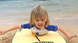 Max on his surfboard at the beach