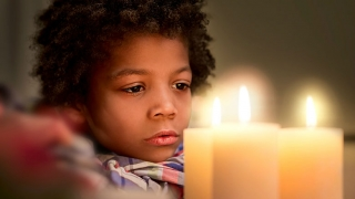Boy looking at lit candles