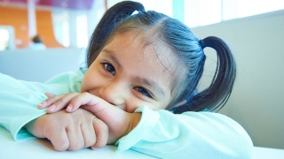 Young girl with pigtails, shy smiling