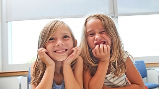 Two smiling young girls sitting at a table