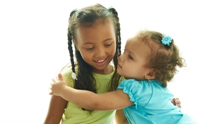 Girl getting a hug from toddler sister.