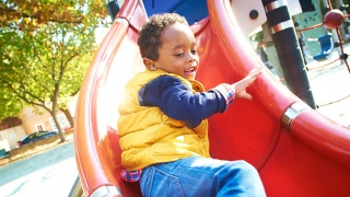 Young boy at bottom of playground slide