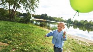 Tommy playing with a baloon at a park
